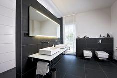 un carrelage noir mat et un sanitaire blanc dans la salle de bains