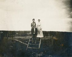 A man and two women stand on a stile of broad wood in the middle of a field. The man stands on the second step, wearing a coat, bow tie, and fedora, the two women stand behind him on top step, wind blowing the skirt against the body of woman in white dress, woman on left has her mouth open in a scream, the wind raising her hair. Halycon Brick Yard is visible in the background.