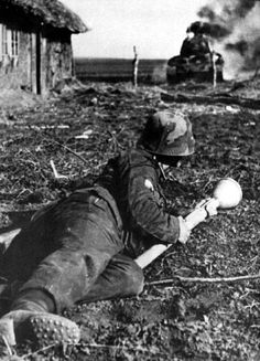 A German soldier watching an enemy tank burn. He is equipped with the Panzerfaust 60, anti-tank rocket.