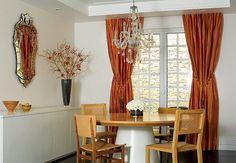 A sala de jantar tem mesa e cadeiras de linhas retas, mas ganha classe e elegância com o lustre de pendentes de cristal, a cortina de seda com volume e o espelho
