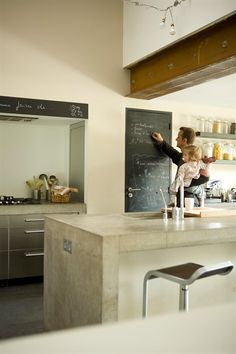 The cement countertops and metallic cabinetry in this design create a structured yet comfortable kitchen