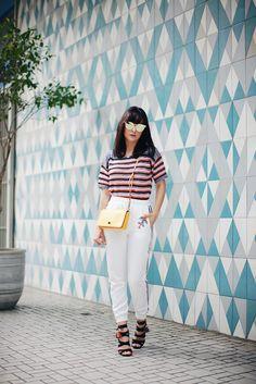 Look da Danielle Noce com calça esportiva branca, salto preto, blusa de tricot listrada e colorida e bolsa amarela.