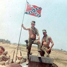 Southern U.S. soldiers wave the rebel battle flag of their ancestors in Vietnam. Date, location, and regiment unknown.