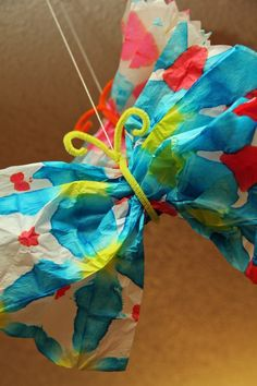 Tie-Dye Butterfly! Use tissue paper, food coloring, pipe cleaners, and rubber bands to make this fun butterfly craft at home!