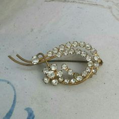 """Vintage Rhinestone Brooch Goldtone rhinestone brooch in a floral motif. C clasp closure, 2 1/2"""" wide, 1 1 / 4 """"  tall. One of the rhinestones is clouded. Priced accordingly. Jewelry Brooches"""