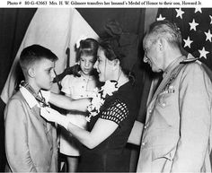 Mrs. Howard W. Gilmore transfers her late husband's Medal of Honor to her son, Howard Jr., at the ceremony in which the medal was posthumously awarded to Commander Gilmore for heroism in action on board Growler (SS-215), on 7 February 1943. Standing by are Commander Gilmore's daughter, Vernon Jeanne, and Rear Admiral Andrew C. Bennett, USN, Commandant, Eighth Naval District. This presentation ceremony took place on 18 August 1943.