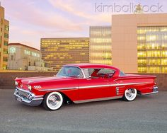 AUT 21 RK1710 01 - 1958 Chevrolet Bel Air Impala Sport Coupe Red Lowrider 3/4 Side View On Pavement By Buildings At Dusk - Kimballstock