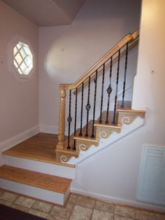 Removed carpet on stairs, took away older style plain iron rail and added new oak treads, painted risers and new banisters and spindles.  Adding a touch of design with the decorative pieces to match treads