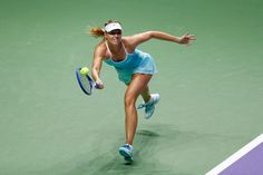 Maria Sharapova Photos Photos - Maria Sharapova of Russia in action against Simona Halep of Romania in a round robin match during the BNP Paribas WTA Finals at Singapore Sports Hub on October 27, 2015 in Singapore. - BNP Paribas WTA Finals: Singapore 2015 - Day Three