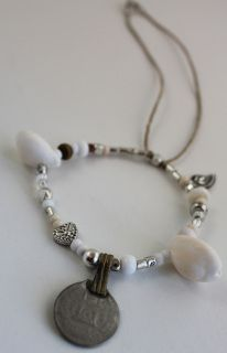 item #B072 Heartbreaker- is a bracelet that is a true statement piece- made of a collection of antique coins, beautiful white cowrie shells, white and clear glass beads, wooden beads, bone beads, silver beads and silver heartbreaker charm on a natural cord.
