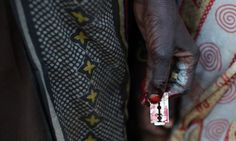A woman holds a razor blade after performing a circumcision on four girls in a village in Kenya. This article is about a woman whose mother refused FGM in the 1970's.