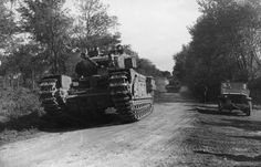Normandy, 1944: A Churchill tank leads a troop of Sherman flail tanks of 79th Armoured Division during the assault on Boulogne, September 1944. A French sailor, who is on secondment with the British as a pathfinder, can be seen manning the radio forward of the Churchill's turret, guiding the vehicles towards their objective.