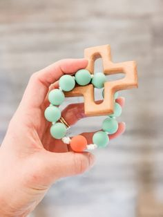 This teething rosary ring is handmade and the recipient was prayed for during its construction by the person that made it. It makes a perfect Baptism gift for a baby boy or a girl. The wooden cross is made by a local Catholic artisan. It is cut from durable maple wood, sanded smooth, and finished with a baby safe and food grade mineral oil/beeswax blend. The beads used are FDA approved food grade silicone. Learn more about the bead safety. This item has been third party tested and meets the safe Catholic Baptism Gifts, The Good Catholic, Teething Beads, Godparent Gifts, Gifts For Boys, Baby Gifts, New Baby Products, Unique Gifts, Food Grade