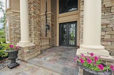 Magnificent Stucco and Stone Mediterranean Exterior Entry & massive Iron Ornate Front Door is absolutely gorgeous.