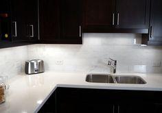 A wonderful pairing... gleaming white quartz countertops and Carrara marble tile backsplash