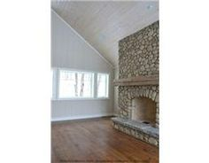 River rock fireplace, whitewashed wood ceiling