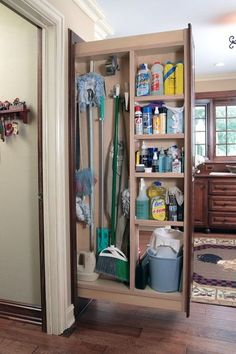 pullout cabinet for mops and broom are shoved in between the refrigerator and cabinets