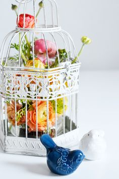 DIY small flower arrangement of ranunculus inside of a decorative birdcage.
