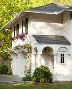 Gorgeous home exterior with window boxes, verandas & pergolas. Love the pergolas over the garage doors.