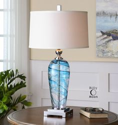 Seaworthy table lamp created of blown blue and clear glass accented with elegant polished nickel plated details. Slightly tapered round hardback shade in a crisp white linen fabric completes this capt