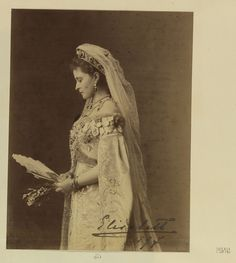 """Grã-duquesa Elisabeth da Rússia de perfil para o lado esquerdo olhando para um fã que ela segura na frente dela. Ela veste uma mantilha de renda. Assinado e datado no canto inferior direito da impressão: """"Elisabeth 1897"""""""
