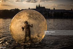 A tourist plays in a zorb ball on the Vltava river (Photo by ) | #Prague #CzechRepublic #zorbball #sunset
