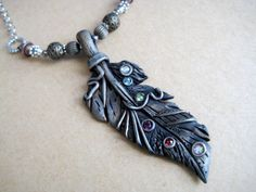 Silver feather pendant made from polymer clay with rainbow crystals. On Etsy by RoyalKitness.