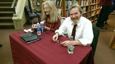 Poets Angela Patten and Daniel Lusk sign copies of their work.