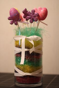 I took this glass and stuffed it with different colored layers of colored grass, aranged the eggs and flowers on stick into the grass, and wrapped the glass in ribon. This project was cheap and easy. I found the flowers and eggs at the dollar store and the colored grass Family Dollar. I already Had the glass piece and the ribbon.
