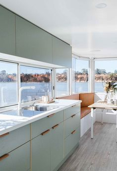 The design of this Australian houseboat features a soft, modern color palette. Here, light sage laminate kitchen cabinets are paired with leather recessed pulls. Kitchen Cabinet Colors, Kitchen Colors, Coloured Kitchen Cabinets, Kitchen Cabinetry, Kitchen Storage, Home Renovation, Laminate Cabinets, Kitchen Laminate, Houseboat Living