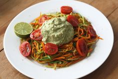carrot and zucchini spaghetti with a creamy avocado sauce and cherry tomatoes