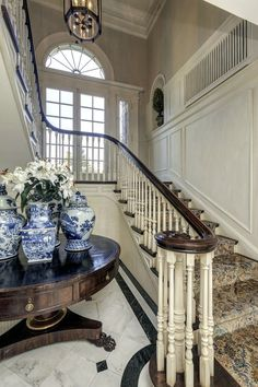 Very impressive neo Georgian foyer and stairs in a spectacular Washington DC home. The millwork, the enormous multipartite picture window on the landing, the marble floors, the collection of blue and white exportware on the antique circular table with clawed feet, the lantern, the feeling of propriety.
