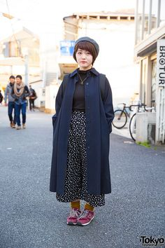 19-year-old Riko on the street in Harajuku wearing a maxi coat with turtleneck, polka dot culottes, New Balance sneakers, and a Vivienne Westwood necklace.