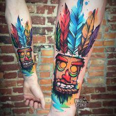 Tatuagem feita por Ewa Sroka da Polônia.    Penas e boneco de madeira colorido no braço.