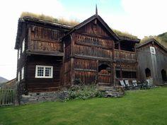 casa con fachada de madera y césped en el tejado