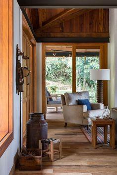 Decoração de casa de campo com madeira. Na sala almofadas azuis, mesa de centro de madeira com adornos, poltrona estofada, tapete listrado, cesto, no corredor objetos decorativos.