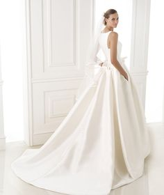Low-waisted princess style dress in mikado silk. Bateau neckline with edging. Bow at the waist with a belt effect.