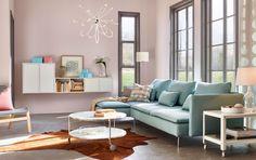Aurinkoinen olohuone, jossa vaaleanturkoosi kolmen istuttava divaanisohva, valkoinen pyöreä sohvapöytä ja pyörällinen tarjoiluvaunu.