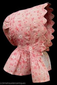 "Girl's pink calico bonnet, American, 1856. An old card pinned inside reads ""This bonnet was made in 1856 and worn by a family of five children. Mrs. Estes Duncan. Made for Luisley Pollod."" Acquired in Lancaster Co., Pennsylvania."