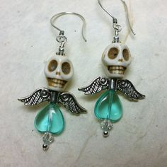 Fabulous and festive winged skull earrings. White howlite skull, pewter wings, aqua blue glass heart, sparkly swarovski crystals, sterling silver accents and earrwire. Measure aprx 2 1/8 from top of earwire to bottom. Could not be cuter or more perfect for the holiday season. Custom requests are always welcome.
