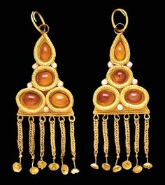 A PAIR OF GERMANIC GOLD AND CARNELIAN EARRINGS  Circa 5th Century A.D.  Each composed of a triangular sheet, set with four cabochon carnelians in plain bezels, each enclosed within an open box topped with granulation, the outer joins of the boxes with a small collar set with white glass, a suspension loop above joined to a circular earwire, the lower edge of the triangle with a border of two opposing twisted wires, and a fringe of six loops each supporting lengths of doubled loop-in-loop…