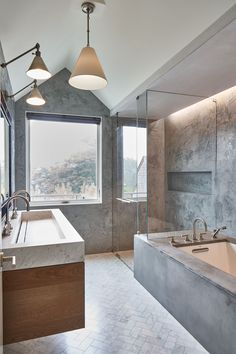 In a bathroom, large, uninterrupted walls of stone, plaster, or concrete can offer a sense of permanence.