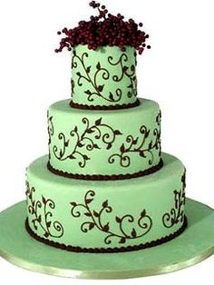 Round three tier brown and green wedding cake decorated with intricate brown scroll work