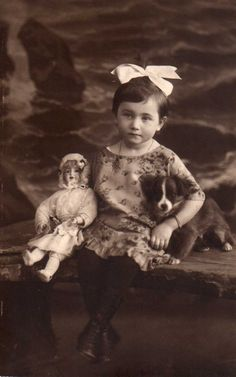 Antique photo of little girl with her doll and pet dog.