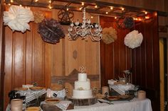 Cake and pie dessert table with vintage chandelier and tissue paper poms at this rustic neutral colored Homestead Chic styled wedding reception at Crazy Man's Hideaway in Veedersburg, IN Cake by Kelly Chaffin
