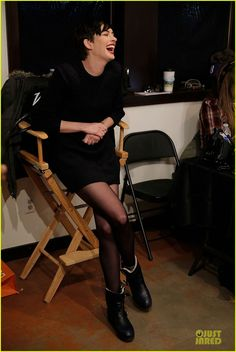 Anne Hathaway, black knit dress, boots and transparent tights.