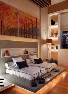 """Relax room. Como tornar um ambiente especialmente relaxante? As arquitetas Paula Costa e Patricia Bicaco apostaram em iluminação cênica, tons claros e conforto nas chaises montadas com futons sobre um tatame de mármore que parece flutuar. """"Preservamos o piso de madeira original e o pé-direito duplo"""", conta Paula, que emoldurou as janelas com prateleiras de laca e fundo de papel que leva toque da palha. A luminária depé Lift, de Fernando Prado, traz uma agradável luz indireta."""