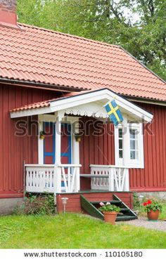 Entrance to a typical red wooden house in Sweden, with swedish flag and friendly flower pots beside the stairs. by almgren, via Shutterstock