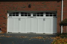 Clopay Coachman Collection carriage style garage door, Design 12 with ARCH3 windows and decorative hardware. www.clopaydoor.com