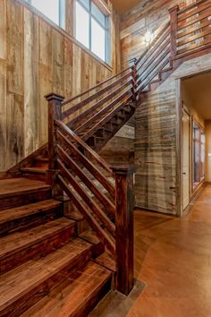 This wooden staircase doesn't need embellishments to make it beautiful. Vertical and horizontal natural wooden boards make up the walls and the stairs' foundation. Stained wood for the stairs and railing create a beautiful contrast. The layered railing creates a smooth and effective support for moving floor to floor.